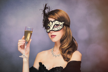 photo of beautiful young woman in mask with wineglass of champagne on the wonderful black studio background