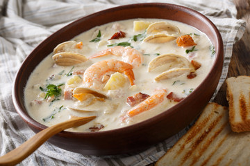 Delicious clam chowder soup with shellfish and bacon close-up on a in a bowl. horizontal
