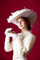 photo of beautiful young woman in vintage dress with plate full of chocolates