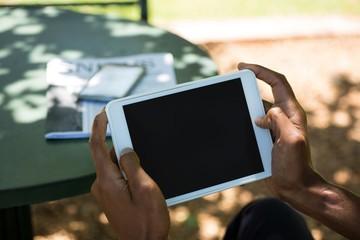 Businessman using digital tablet at outdoor restaurant