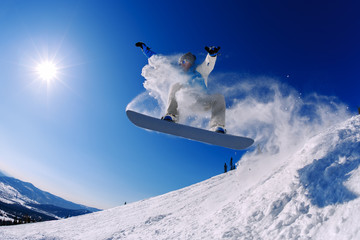 Snowboarder jumping from the springboard against the sky