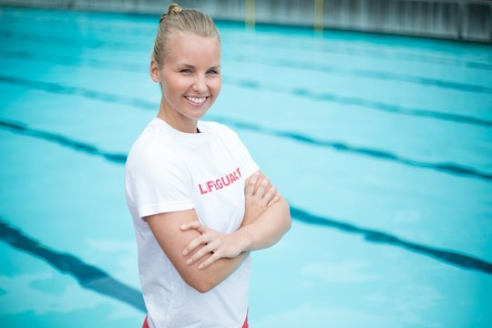 Happy female lifeguard standing at poolside