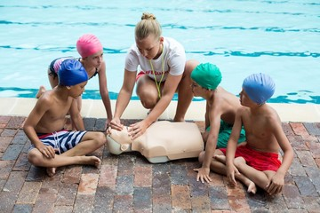 lifeguard giving rescue training to children at poolside