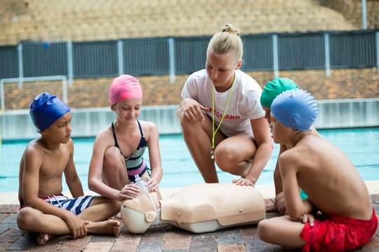 Lifeguard assisting children during rescue training