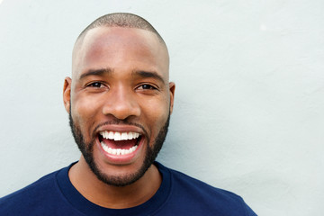 cheerful young african man laughing against white wall