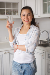 Young beautiful woman standing at kitchen with glass of clean pure filtered water and smiling. Cheerful girl indoors drinking water and quenching her thirst