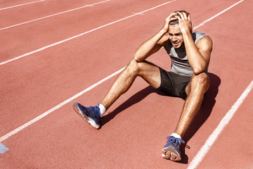 Young male athlete looking upset and devastated after losing in a competition