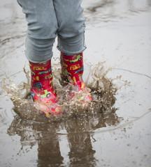dziecko w kaloszach bawiące się w deszczu