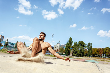 Male athlete performing a long jump
