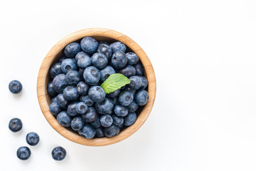 Bowl of fresh blueberries isolated on white, top view copy space