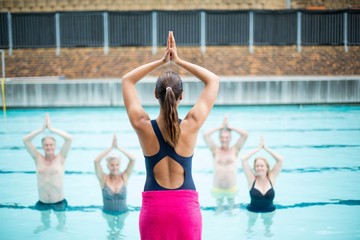 Yoga instructor assisting senior swimmers at poolside