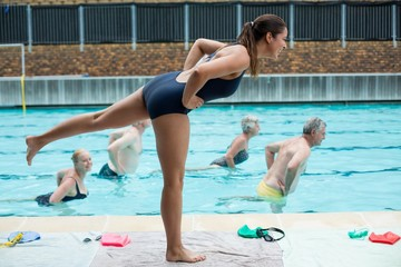 Young female trainer assisting senior swimmers