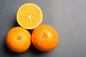 Three oranges on grey background