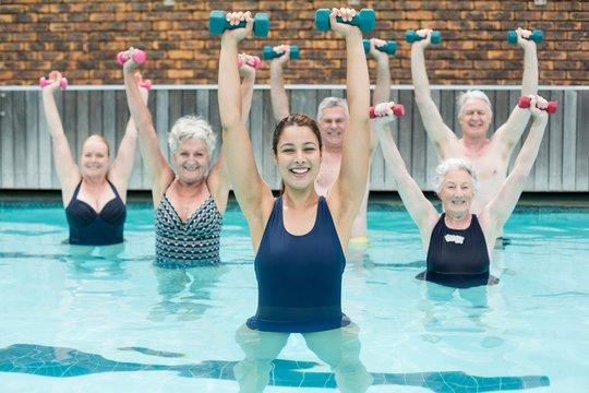 Senior swimmers lifting dumbbells in swimming pool