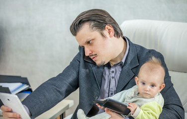 A busy businessman is trying to work and is talking on the phone while also trying to spend some time with his baby.