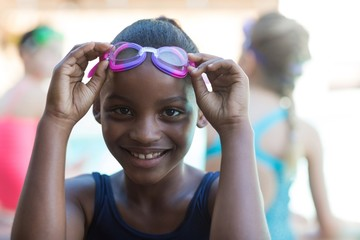 Portrait of smiling girl holding swimming goggles