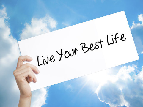 Live Your Best Life Sign on white paper. Man Hand Holding Paper with text. Isolated on sky background