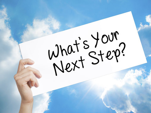 What's Your Next Step? Sign on white paper. Man Hand Holding Paper with text. Isolated on sky background