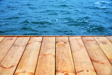 Wooden board empty floor in front of blue water sea background