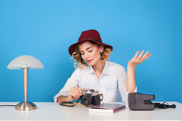 Happy young hipster girl photographer sitting at the table with her equipment.woman in red hat,blue background,happy face,girl with camera,curly hair,attractive woman,traveler girl