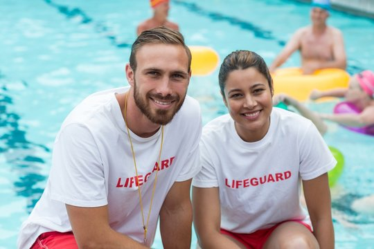 Male and female lifeguards crouching at poolside