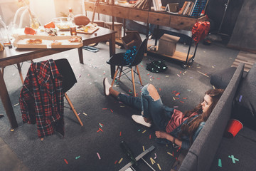 High angle view of drunk young woman lying on floor in messy room after party