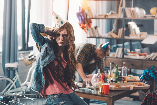 confused woman in birthday hat, man cleaning behind in messy room after party