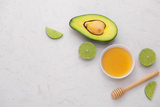 Healthy food concept. Fresh organic avocado and lime with honey on table