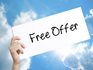 Free Offer  Sign on white paper. Man Hand Holding Paper with text. Isolated on sky background