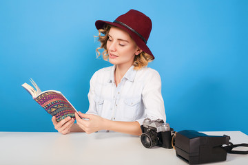 Happy young hipster girl photographer read notebook at the table with her equipment.woman in red hat,blue background,happy face,girl with camera,curly hair,attractive woman,traveler girl