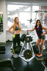pair of young athletic women in a gym, posing with sports equipment with a smile on their faces