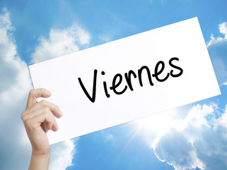 Viernes (Friday in Spanish) Sign on white paper. Man Hand Holding Paper with text. Isolated on sky background