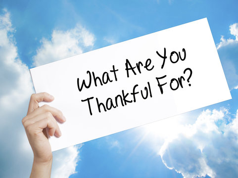 What Are You Thankful For? Sign on white paper. Man Hand Holding Paper with text. Isolated on sky background