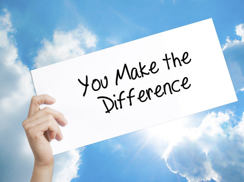You Make the Difference Sign on white paper. Man Hand Holding Paper with text. Isolated on sky background