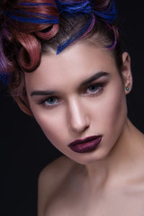 Beautiful girl with bright creative fashion makeup and colorful hairstyle. Studio portrait of beauty face.