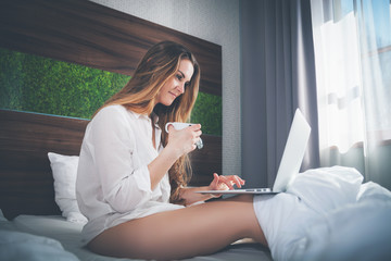Pretty woman on bed in modern apartment using laptop and drinking coffee after wake up