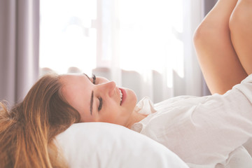 Pretty woman on bed in modern apartment smiling after wake up