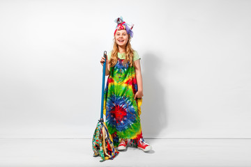 Happy blonde child girl in hippie colorful dress against white wall