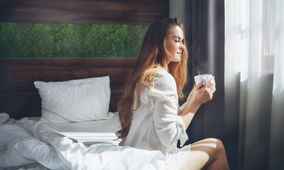 Pretty woman in modern apartment drinking coffee after wake up