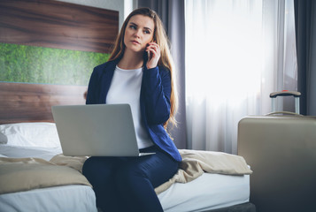 Business woman with suitcase in modern hotel room using laptop and smartphone