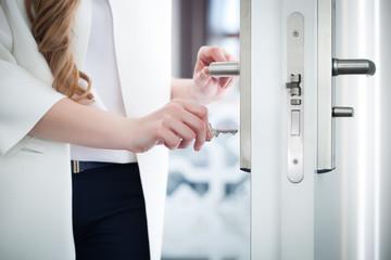 Locking or unlocking door with key in hand