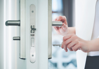 Locking or unlocking door with key in hand