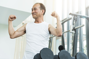 Asian senior man  working out at the gym. copy space.