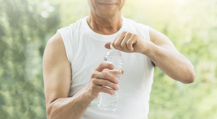 Close up Asian senior man holding bottle of water at a gym. Drinking water. Tired, thirstily. freshness.