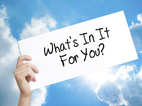 Whats In It For You? Sign on white paper. Man Hand Holding Paper with text. Isolated on sky background