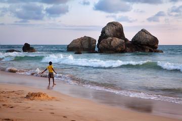 Мальчик гуляет по пляжу.