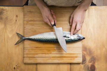 魚を調理する女性の手
