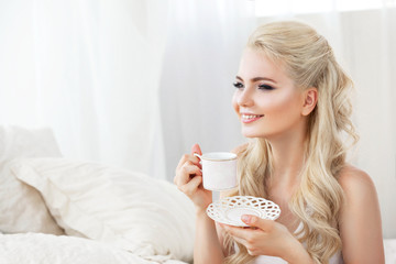 Beautiful young smiling woman sitting on white bed , holding a cup of coffee