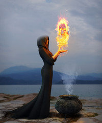 Portrait of a young witch creating a burning skull
