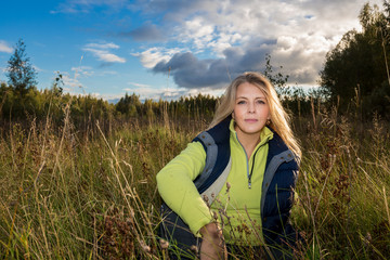 Pretty blonde woman among grass in the summer field